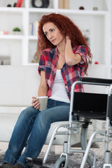 cheerful disabled woman holding hot coffee cup at home