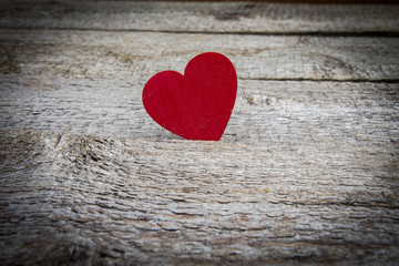 Red wooden heart on rustic background.