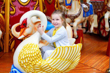 Adorable little girl playing on carousel at amusement park