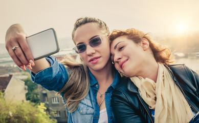 Two beautiful friends making selfie