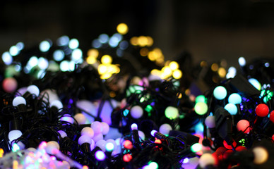 LED lights garland on table colorful light bulbs on a dark bokeh Christmas and Happy New Years decoration background