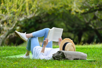 Happy woman lying on green grass reading a book in the park (outdoors)