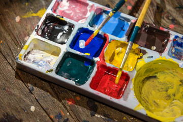 Colorful colors palette and paint brushes on dirty wooden artist table