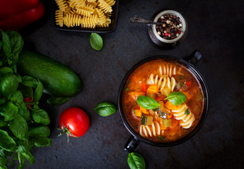 Minestrone, italian vegetable soup with pasta on black backgrounds. Top view