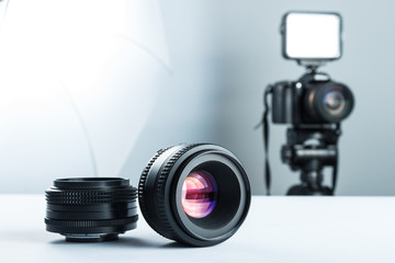 Set of DSLR lenses on a white table in stuidio, against the background of the DSLR camera to light and softbox.