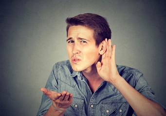 hard of hearing man placing hand on ear asking someone to speak up