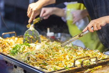 Asian street food - people cooking some food in Seoul - South Korea. Noodle with vegetables