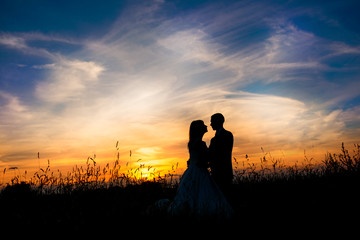 Romantic wedding couples kiss at sunset