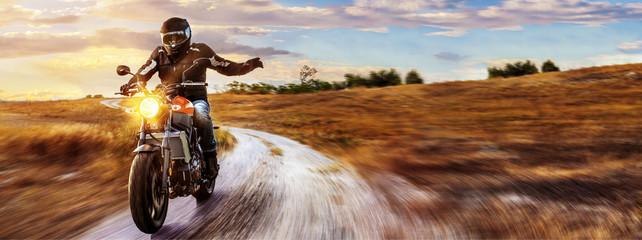 Motorrad fährt auf freier Landstrasse in den Sonnenuntergang