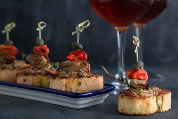 Pintxos Tapa on traditional plate, crispy bread, tuna, onion and pepper