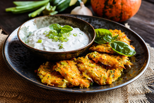 Pumpkin pancakes with zucchini and served with sour cream dip