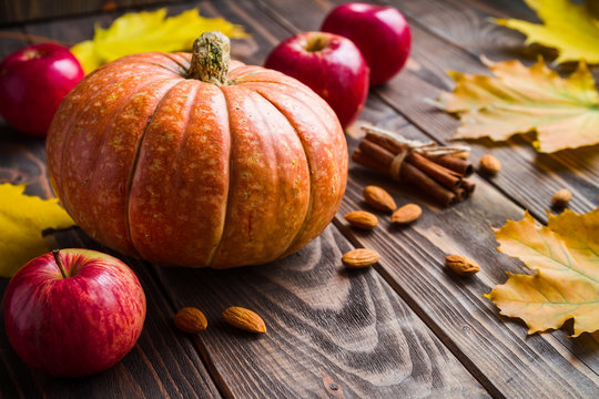 wood background with pumpkin, apples, maple leafes, nut and cinn