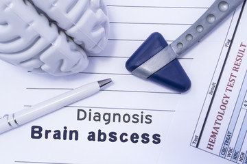 Diagnosis Brain Abscess. Figure brain, neurological hammer, printed on a paper blood test and written diagnosis of Brain Abscess in the medical form is lying on the table in the neurologist cabinet