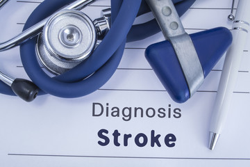The diagnosis of stroke. Paper medical history with diagnosis of stroke, on which lie blue stethoscope, neurological hammer and pen. Medical concept for stroke for neurology and neuroscience