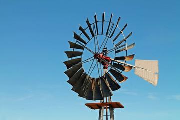 Metal Windmill Blade Against a Bright Blue Sky