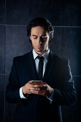 Handsome stylish young man writing sms on phone
