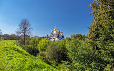 Golden cupola of orthodox church of Dmitrov Kremlin in summer under clear blue sky surrounded by green trees