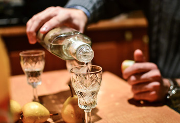Man pouring strong alcoholic drink vodka in glass