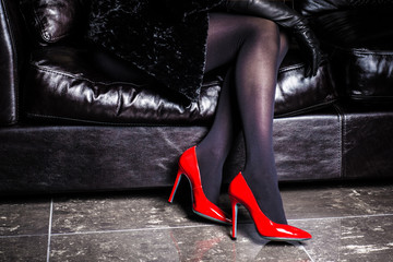 woman legs with heels pointing up isolated on a couch