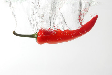 Fotobehang Hot chili peppers red chili pepper falling in water