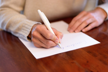 Woman sitting writing on a sheet of white paper