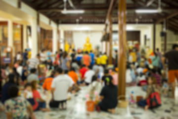 blurred image with people make something good in temple for back