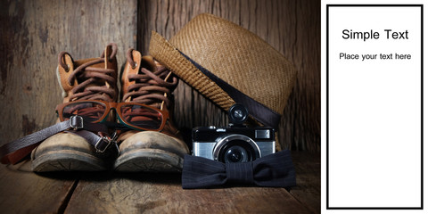 Vintage boots, hat and accessories for travel on a wooden background with black space for text