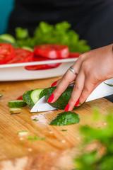 Women's hands cut fresh vegetables.