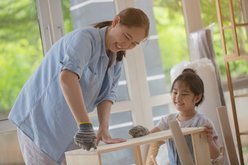 Asian lovely girl helping her mother assembling new DIY furniture at home together