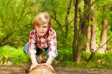 Portrait of blond young boy standing on a log