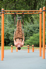 Muscular man exercising on outdoor gymnastic ring.