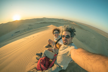 Adult couple taking selfie on sand dunes in the Namib desert, Namib Naukluft National Park, main travel destination in Namibia, Africa. Fisheye view in backlight, toned image. Wall mural