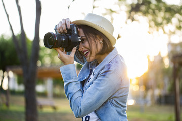 Young woman making photos with professional camera at summer gre
