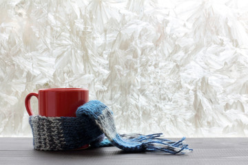 winter warming drinks/ red mug wrapped a woolen scarf near a window decorations frost