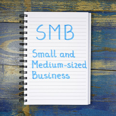 SMB- Small And Medium-sized Business acronym written in notebook on wooden background