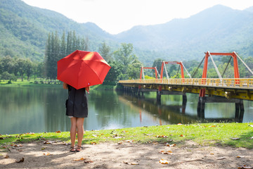 A woman with red umbrella standing on the port and looking a bridge