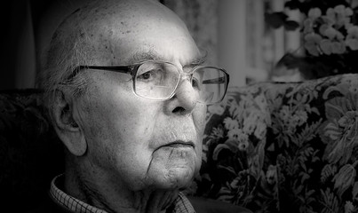 Portrait of 95 years old English man sitting in chair in domestic environment. Black and white