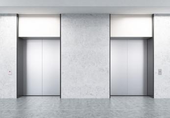 Two closed elevators in corridor with concrete walls