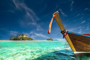 Thai traditional wooden boat with ribbon decoration at ocean shore near Koh Tup island. Thailand, Krabi province, Ao Nang