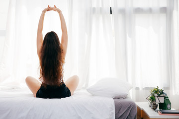 Back of young woman sitting and stretching up on bed in the morning