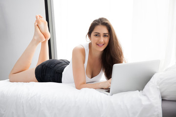 Beautiful Caucasian woman laying down on white bed using laptop and smile
