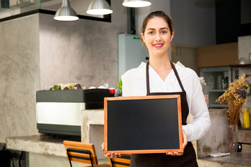 Beautiful Caucasian woman in barista apron holding empty blackboard sign inside coffee shop - ready to insert text