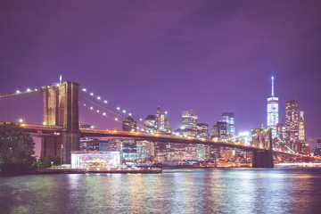 Wall Mural - New York City skyline and Brooklyn Bridge at night with light and vintage toned filter effect