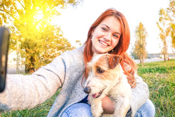 Young woman and dog taking selfie with mobile phone in a park - Concept of human and pet friendship