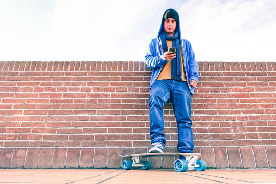 Hooded man using phone standing on skateboard - Serious teenager looking down to mobile smartphone leaning on urban wall background