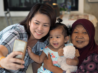 Asian family taking photo with smart phone, Baby girl, Grandmoth