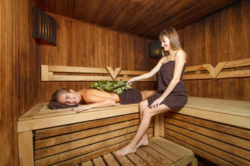 Two females in a sauna.