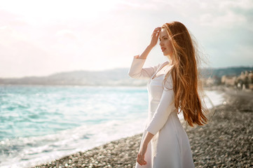Outdoor summer portrait of young pretty woman with great hair looking to the ocean at europe beach, enjoy her freedom and fresh air, wearing stylish white dress.