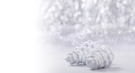 Silver and white Christmas ornaments on glitter bokeh background with space for text. Xmas and Happy New Year theme