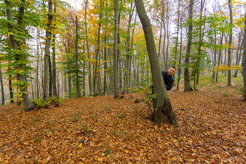 man hiding behind the tree in the forest